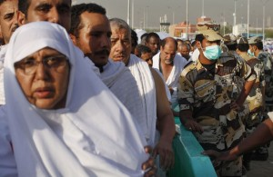 Saudi security forces look on as Hajj pilgrims are pass by.