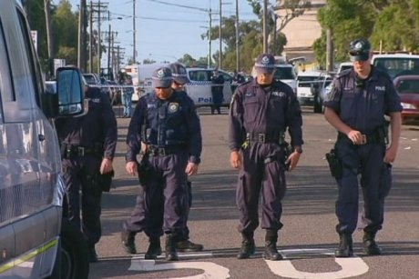 PHOTO Police officers scour Rosedale Avenue in Greenacre for evidence during the day after a man was shot outside an Islamic Centre.