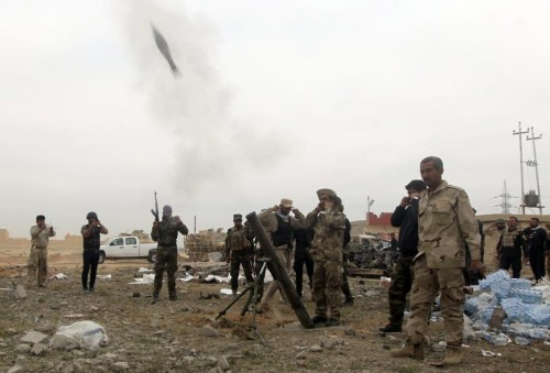 Iraqi Shiite fighters of the government-controlled Popular Mobilisation units launch mortar shells towards the Islamic State group in the city of Tikrit on March 12, 2015, during a military operation to retake the city (AFP Photo/Ahmad Al-Rubaye)