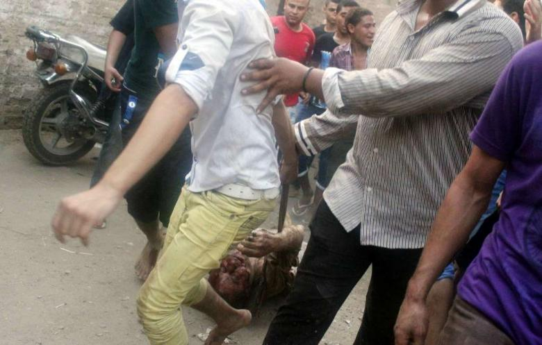 On 23 June 2013 several villagers in Giza, Egypt were killed in an anti-Shi'a attack. One of the bloodied Shi'a victims is being dragged on the streets in this photo. (Photo: AFP - STR)
